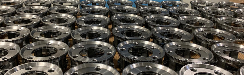 A grid of machined steel parts with gear teeth and mounting holes.
