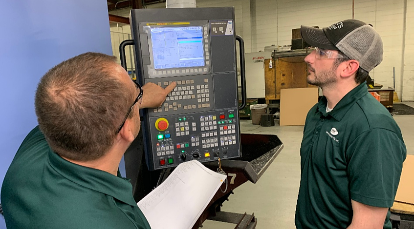 Two Stecker employees programing a CNC Machine with G-Code
