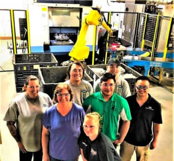 Seven manufacturing floor employees at stacker in front of robot cell